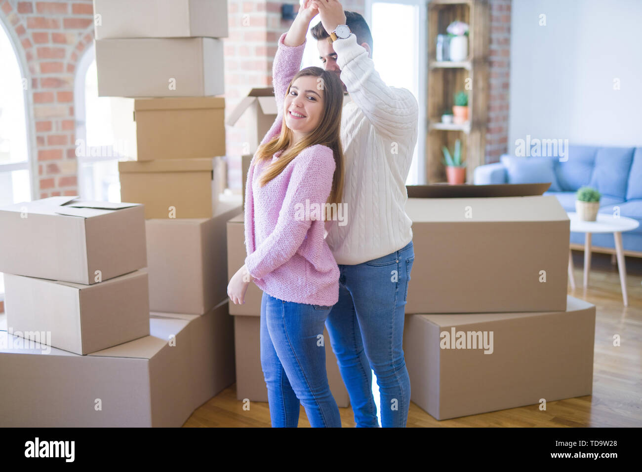 Young beautiful couple in love celebrating dancing moving to a new home, smiling very happy for new apartment - Stock Image