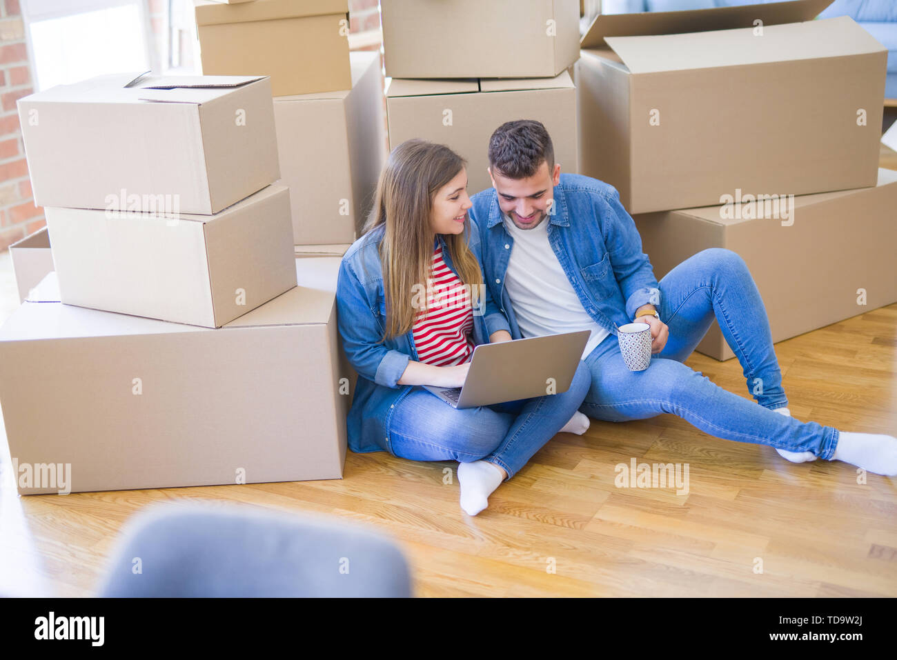 Young couple sitting on the floor around cardboard boxes using computer laptop, very happy moving to a new house - Stock Image