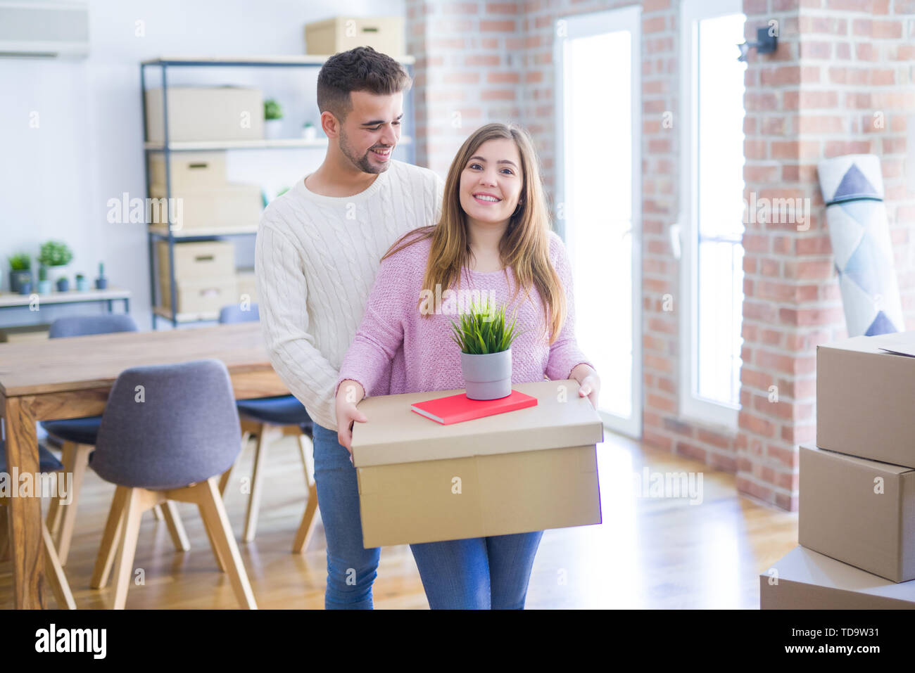 Young beautiful couple in love moving to new home, holding cardboard boxes very happy and cheerful for new apartment - Stock Image