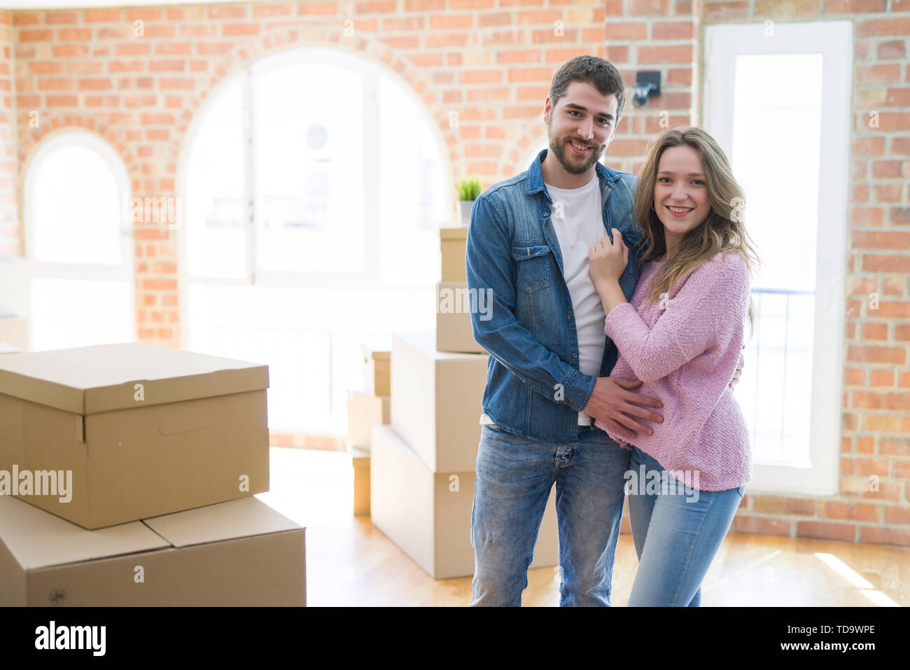 Young beautiful couple looking happy together moving to a new home - Stock Image