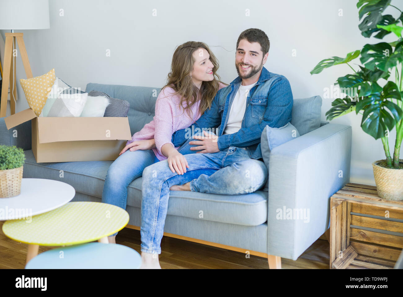 Young couple in love hugging sitting on the sofa very happy moving to a new home - Stock Image