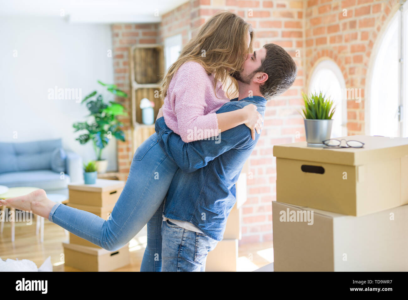 Young beautiful couple in love celebrating moving to a new home around cardboard boxes - Stock Image