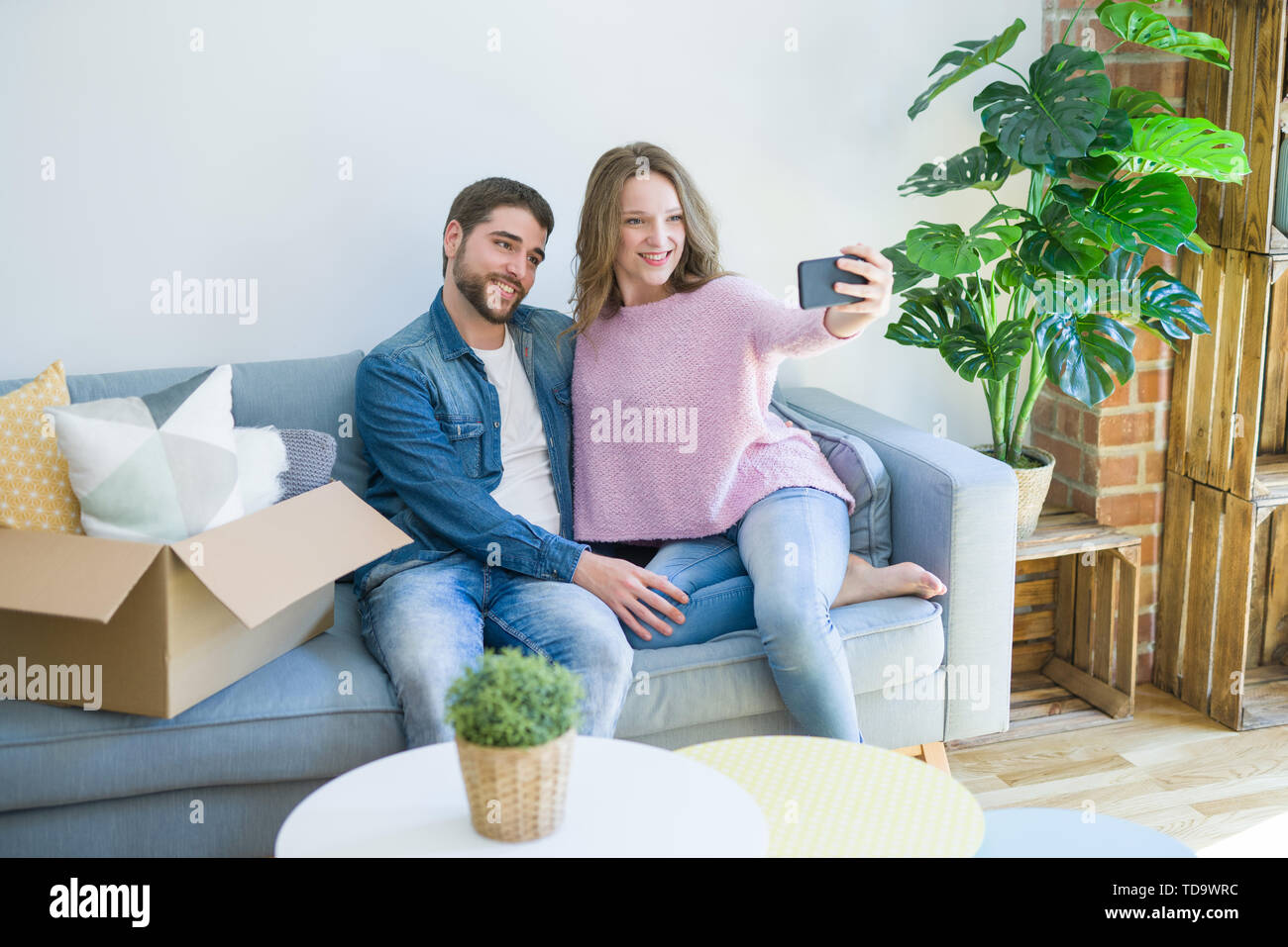Young beautiful couple taking a selfie photo using smartphone sitting on the sofa smiling very happy for moving to a new home - Stock Image