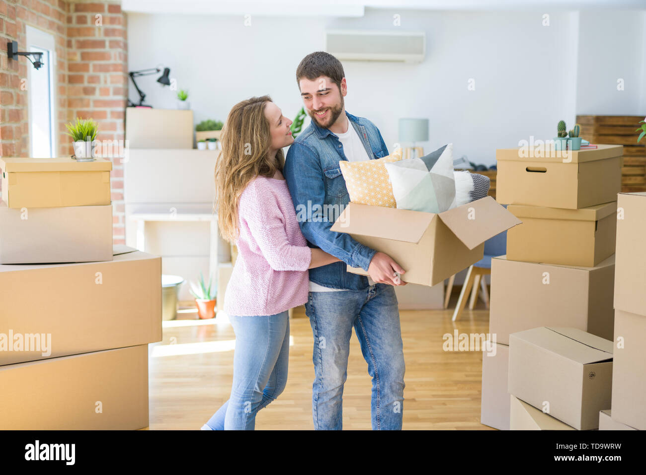 Young beautiful couple very happy together holding cardboard boxes moving to a new home - Stock Image