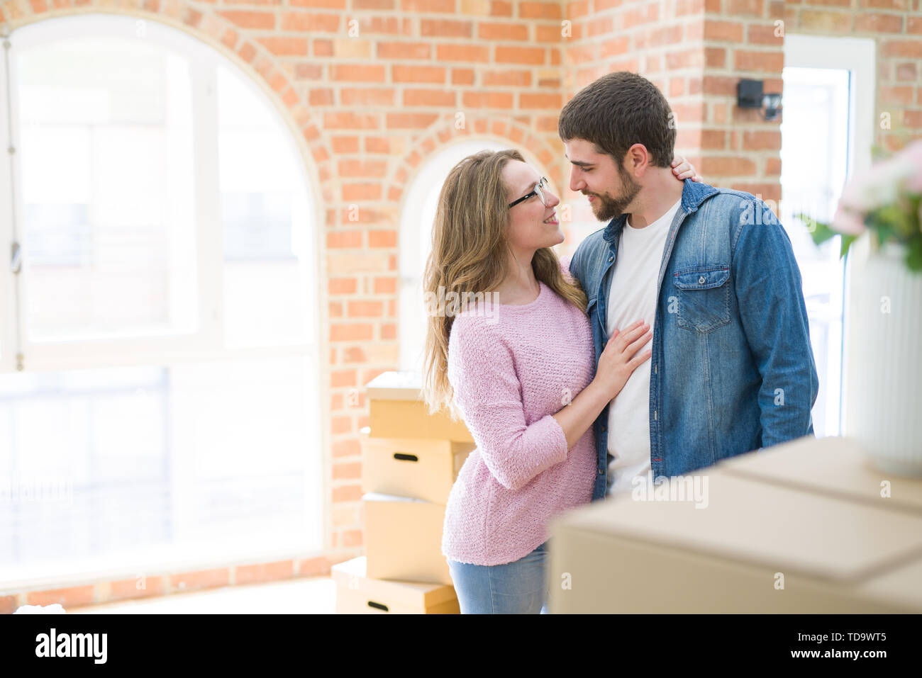 Young couple around cardboard boxes very happy moving to a new home - Stock Image