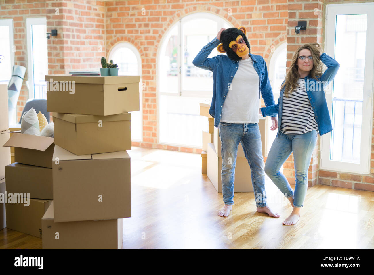 Young couple having fun wearing a monkey mask moving to a new apartment around cardboard boxes - Stock Image