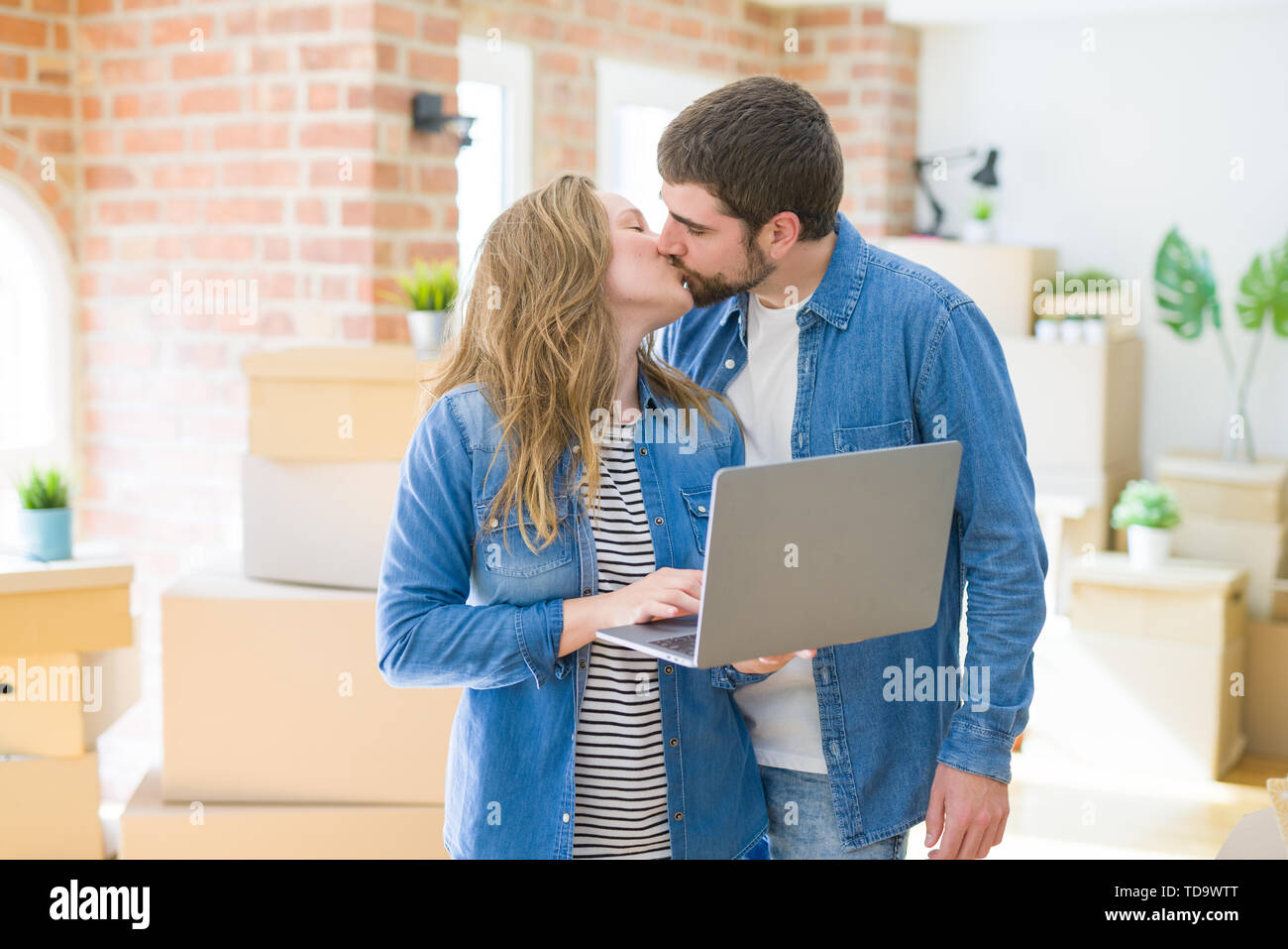 Young couple using computer laptop standing on a room around cardboard boxes, happy for moving to a new apartment - Stock Image