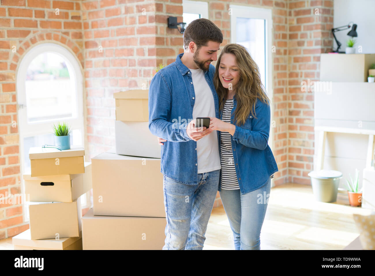 Young couple moving to a new house using smartphone around cardboard boxes - Stock Image