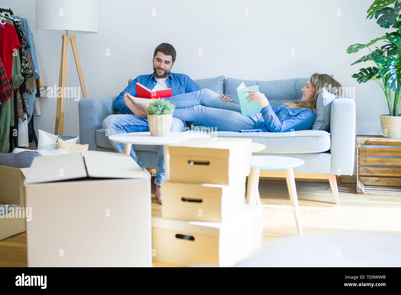 Young couple relaxing on the sofa reading a book, taking a break for moving to new house - Stock Image