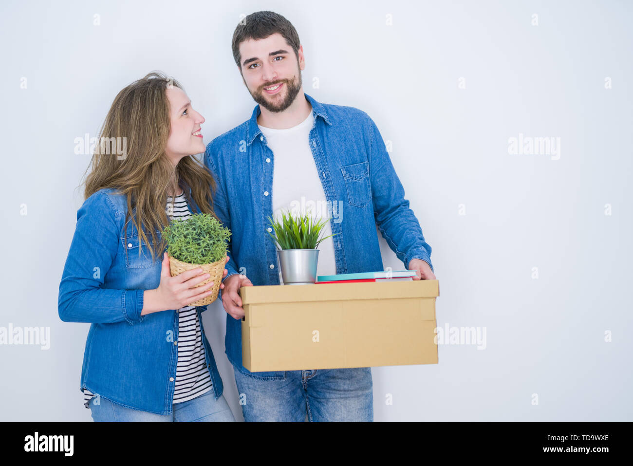 Young beautiful couple holding cardboard boxes very happy for moving to a new home over white isolated background - Stock Image