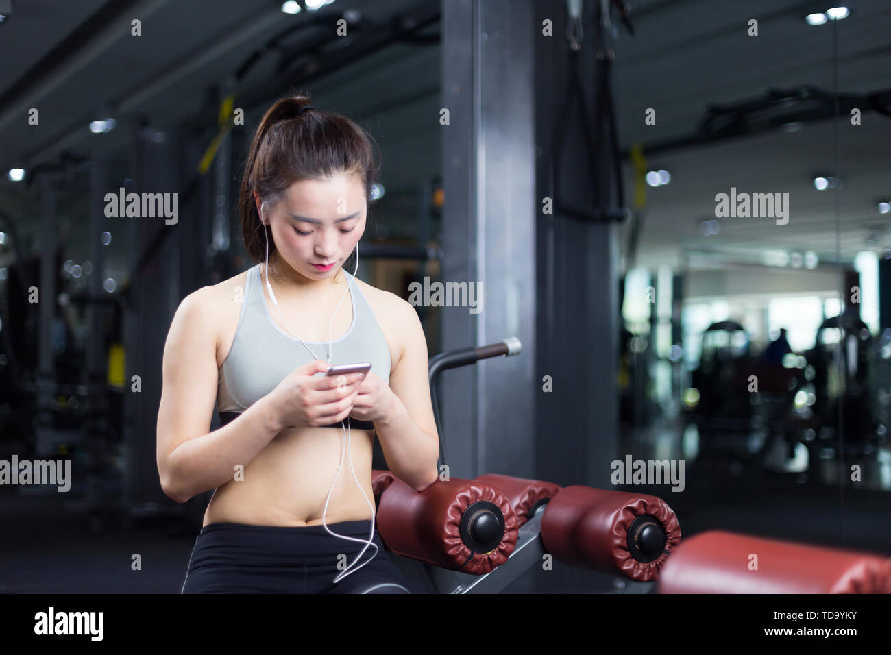 young asian girl with smart phone in modern gym - Stock Image