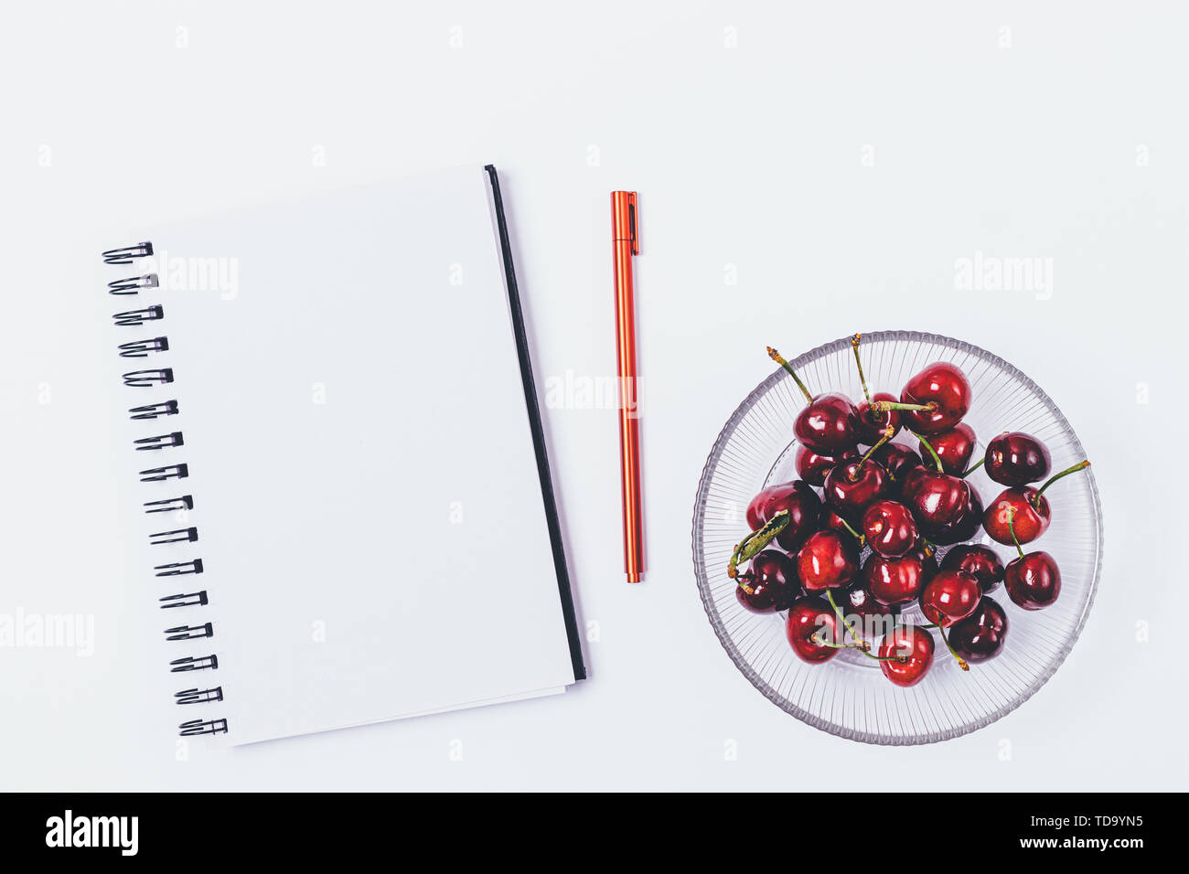 Top view of desk with empty notebook and pen next to healthy snack of fresh cherries, flat lay on white background. - Stock Image