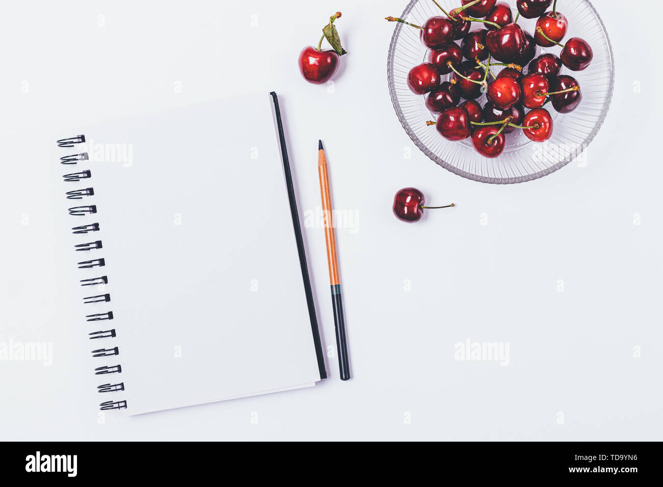 View from above of table with blank notepad and pencil next to healthy snack of fresh cherries, flat lay on white background. - Stock Image