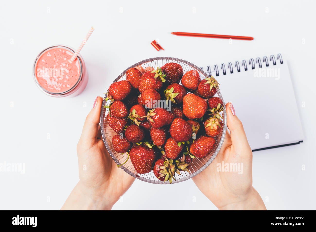 Woman's hands holding bowl of fresh strawberries above white table with empty notebook and smoothie, flat lay. - Stock Image