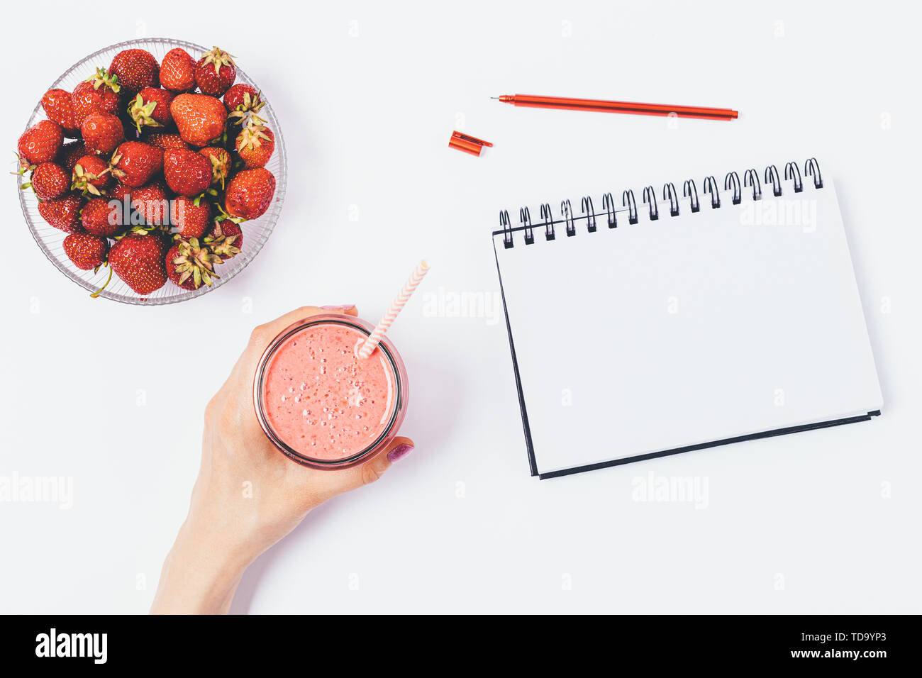Female hand holding delicious strawberry smoothie next to bowl of fresh berries and an empty notepad on white desk, flat lay. - Stock Image