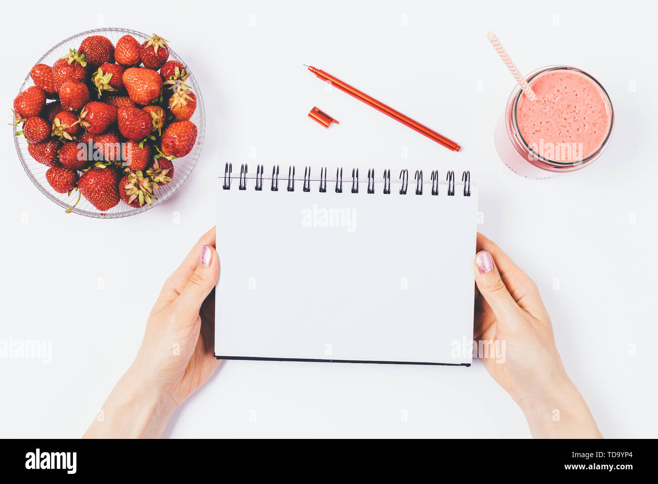 Flat lay arrangement of woman's hands holding empty notebook next to bowl of fresh strawberries and smoothie on white background, top view. - Stock Image