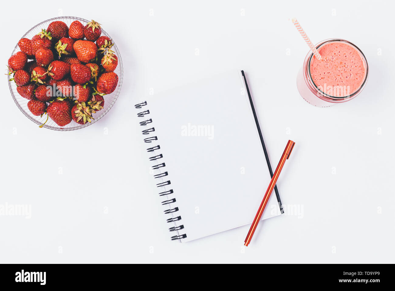 Flat lay arrangement of empty notebook journal with pen next to bowl of fresh strawberries and smoothie on white background, top view. - Stock Image