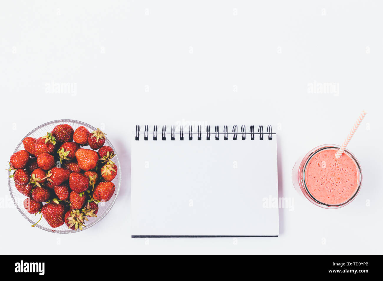 Bowl of fresh strawberries, clean notepad sheet and smoothie with straw on white background, flat lay composition with copy space. - Stock Image