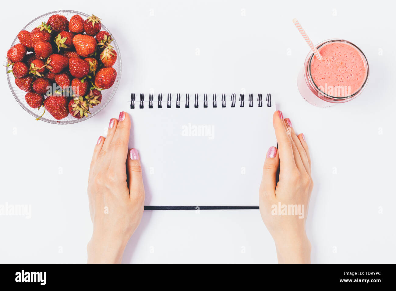 Woman's hands holding blank journal sheet near bowl of fresh strawberries and smoothie with straw on white background, flat lay composition. - Stock Image
