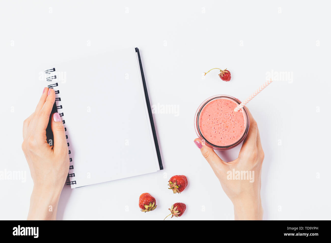 Woman's hands holding an empty notepad and glass of strawberry smoothie next to berries on white table, top view. - Stock Image