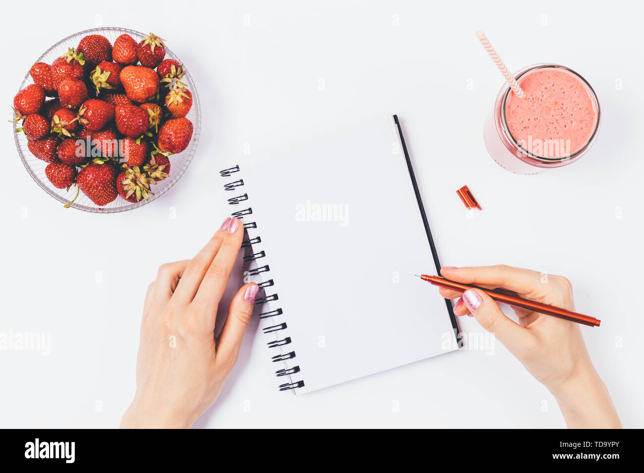 Flat lay arrangement of woman's hands writing in empty notebook next to bowl of fresh strawberries and smoothie on white background, top view. - Stock Image
