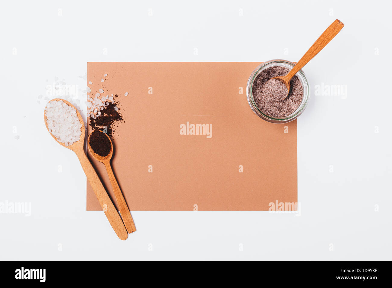 Homemade anti-cellulite coffee scrub with sea salt near jar of fresh made product on white background, flat lay mockup. - Stock Image