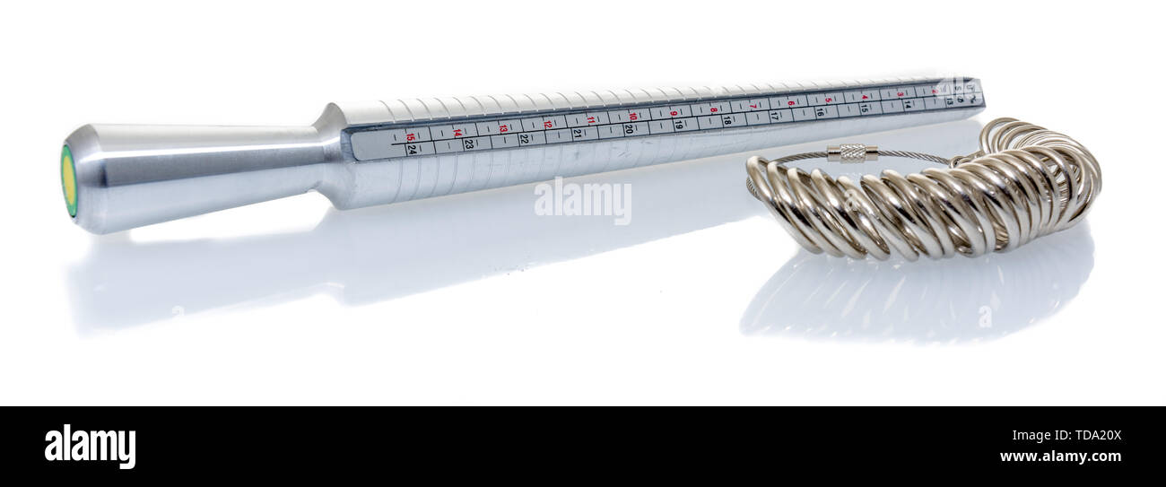 A ring sizer and rings for measuring fingers for ring size on an isolated background. - Stock Image