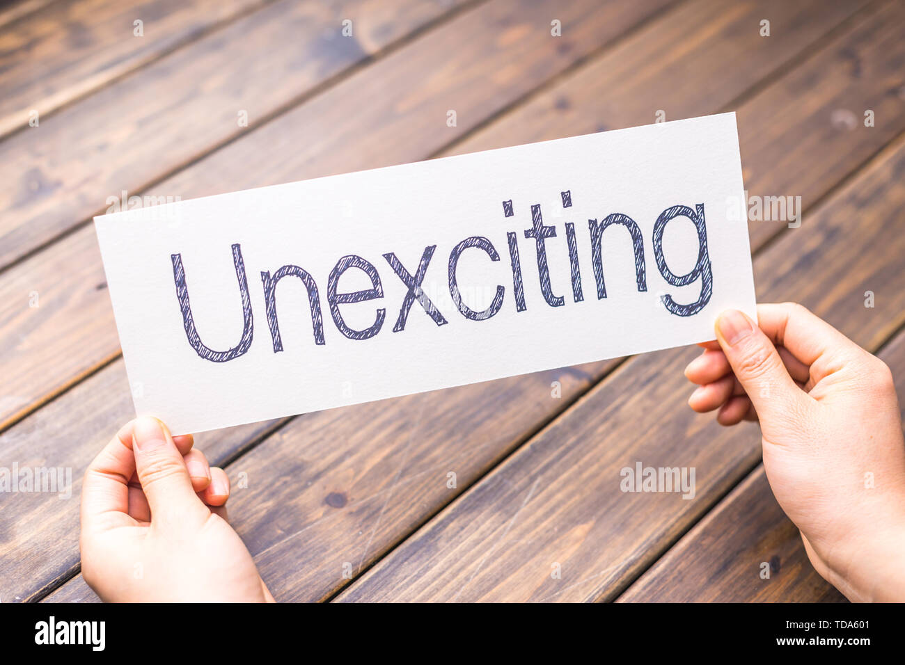 hands hold white paper with word unexciting Stock Photo