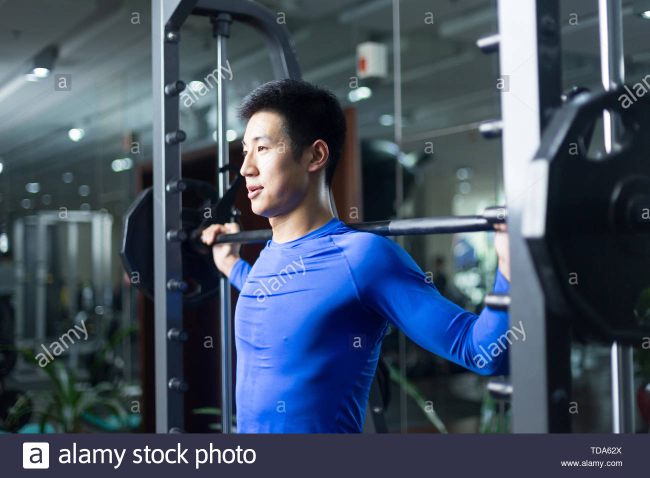 young asian man working out in modern gym - Stock Image