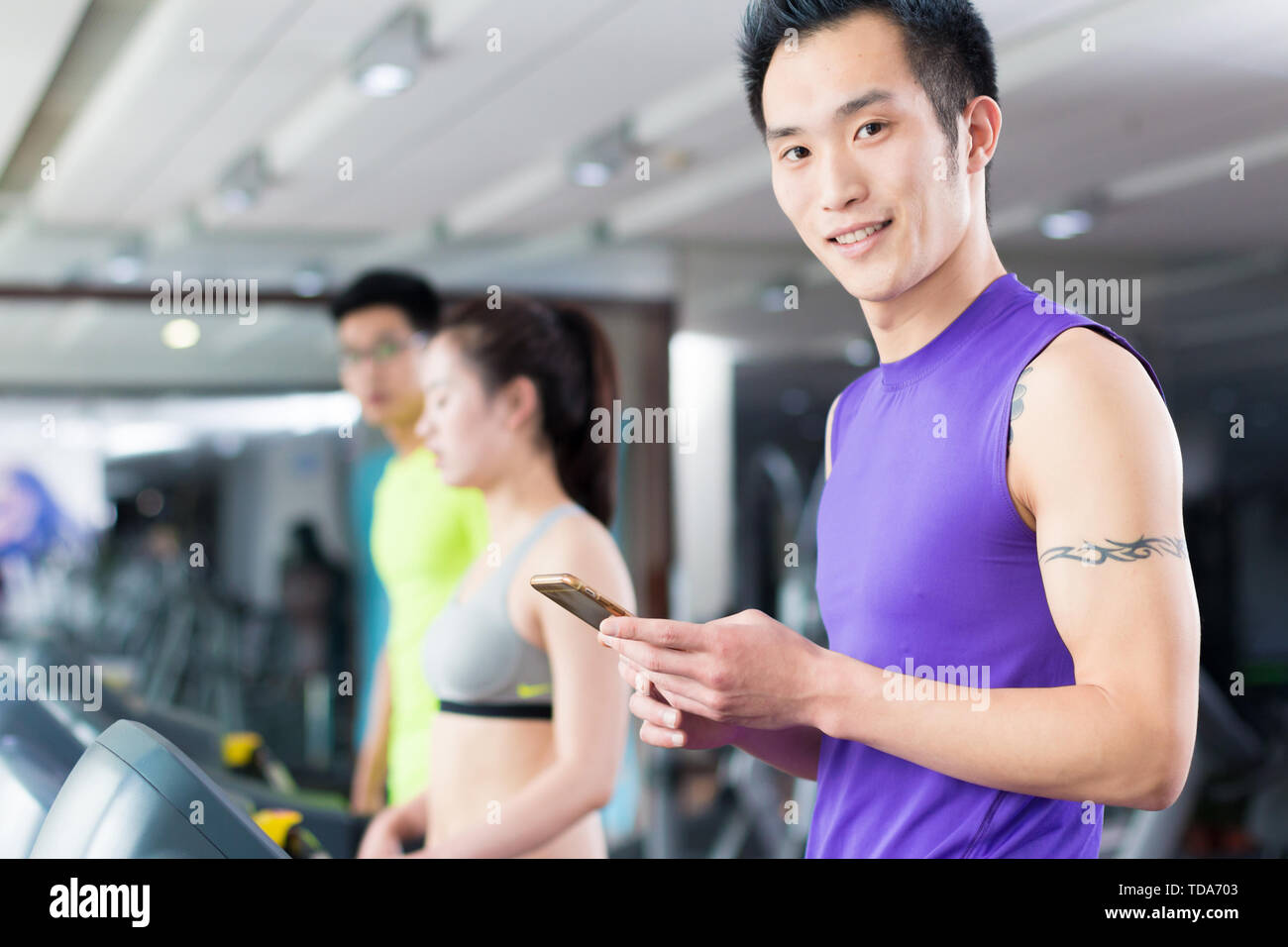 young asian people working out in modern gym - Stock Image