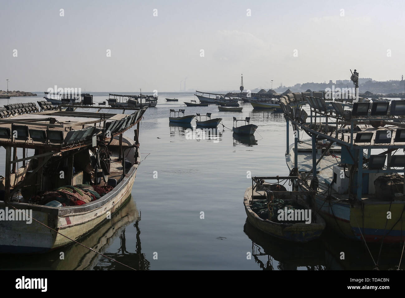 Gaza City, Palestinian Territories. 14th June, 2019. Palestinian fishing boats anchored in Gaza port and fish shops empty. According to media reports, Israel closed the fishing area of Gaza fishermen until further notice in response to the so-called four burning balloons that emerged from the coastal enclave creating small fires In southern Israel. Credit: Mohammed Talatene/dpa/Alamy Live News - Stock Image