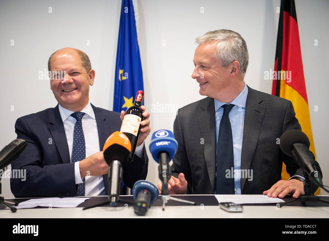 Luxemburg, Germany. 14th June, 2019. Olaf Scholz (SPD, l), Federal Minister of Finance, is holding a wine bottle in his hand which he received from Bruno Le Maire (r), Minister of Economic Affairs of France, as a birthday present before a joint press conference on the occasion of the Eurogroup meeting. At the meeting on Friday night, the finance ministers of the euro countries made progress on the controversial euro zone budget. Credit: Arne Immanuel Bänsch/dpa/Alamy Live News - Stock Image