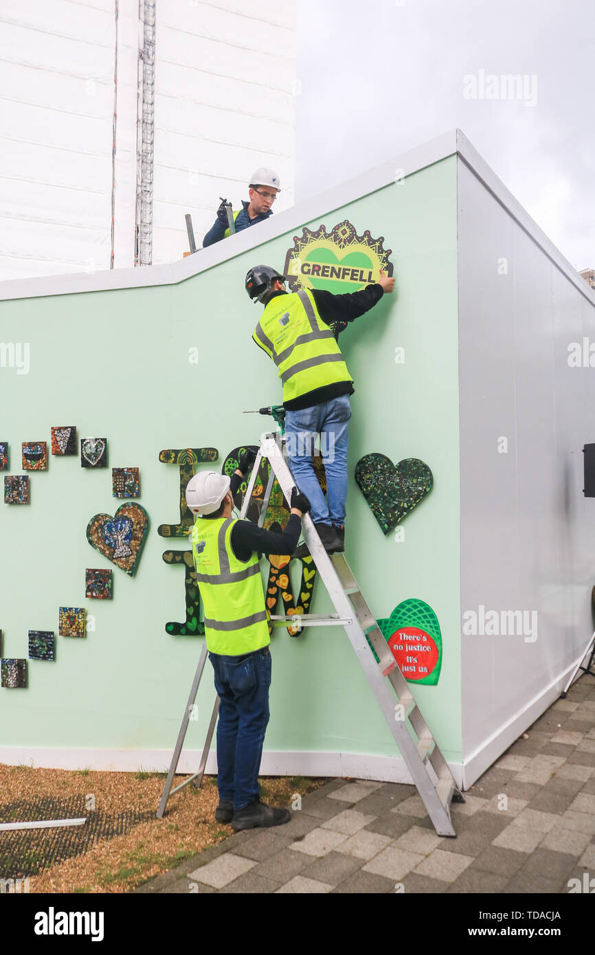 London, UK. 13th June, 2019. Workers attach hearts at the memorial to the Grenfell fire victims on the second anniversary of the devastating inferno fire which in the residential tower block in West London Credit: amer ghazzal/Alamy Live News - Stock Image