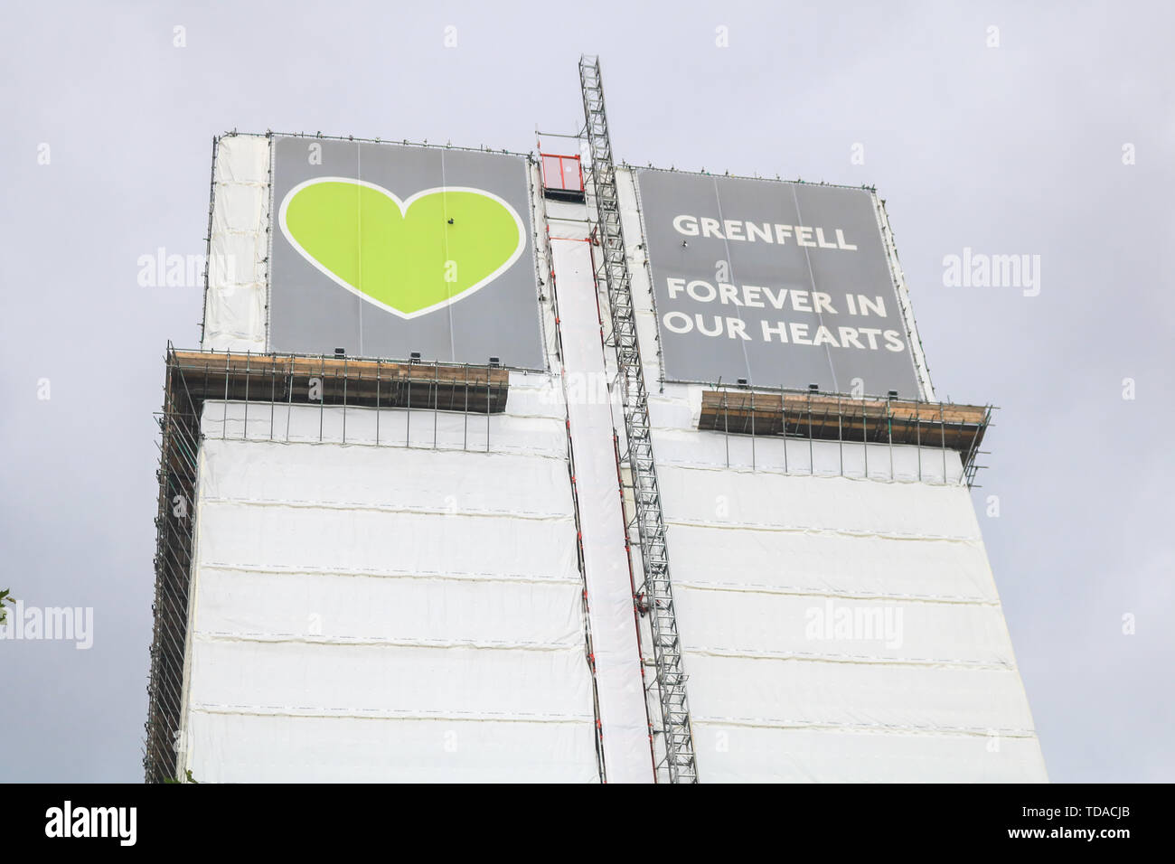 London, UK. 13th June, 2019. The Grenfell tower covered in white tarpualin wirth a message 'Grenfell Forever in Our Hearts on the second anniversary of the devastating inferno fire which in the residential tower block in West London Credit: amer ghazzal/Alamy Live News - Stock Image