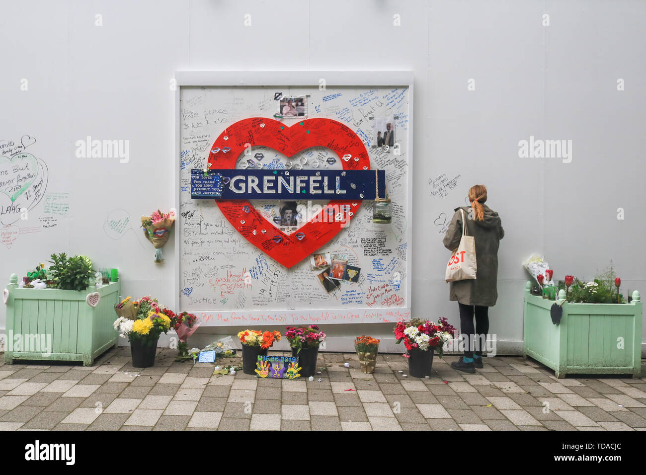 London, UK. 13th June, 2019. A member of the public writes a message at the memorial to the Grenfell fire victims on the second anniversary of the devastating inferno fire which in the residential tower block in West London on 14 June 2017 Credit: amer ghazzal/Alamy Live News - Stock Image