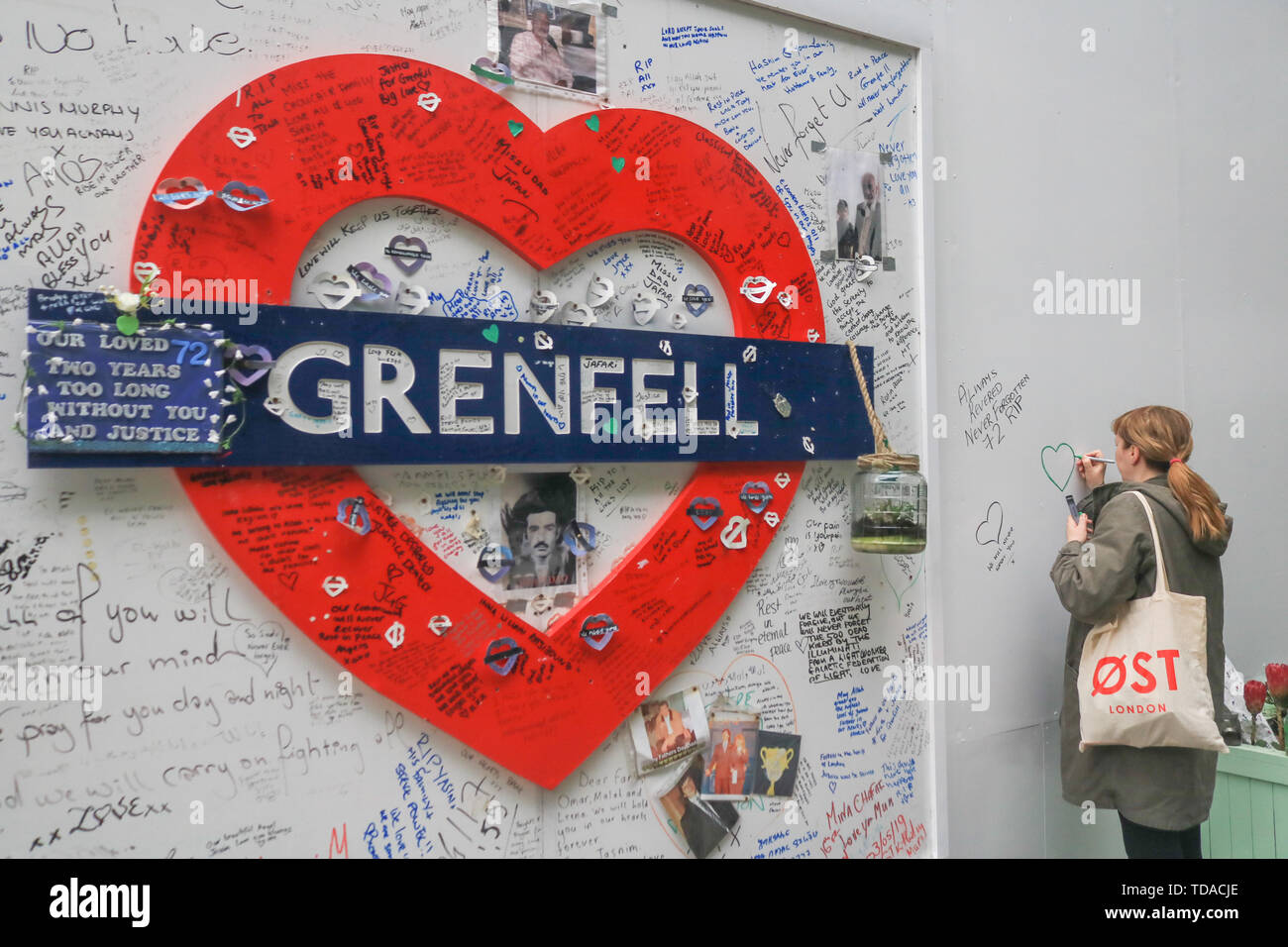 London, UK. 13th June, 2019. A member of the public writes a message of sympathy at the memorial to the Grenfell fire victims on the second anniversary of the devastating inferno fire which in the residential tower block in West London on 14 June 2017 Credit: amer ghazzal/Alamy Live News - Stock Image