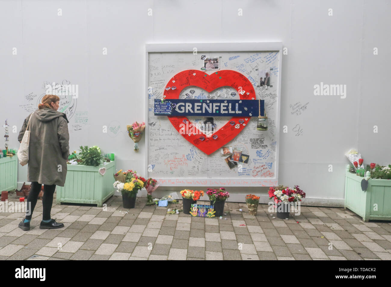 London, UK. 13th June, 2019. A member of the public views the memorial to the Grenfell fire victims on the second anniversary of the devastating inferno fire which in the residential tower block in West London on 14 June 2017 Credit: amer ghazzal/Alamy Live News - Stock Image