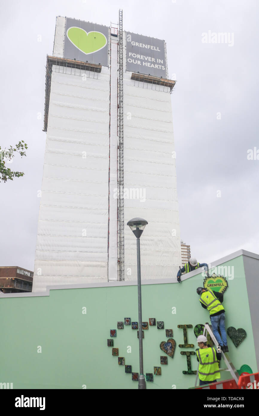 London, UK. 13th June, 2019. Workers attach hearts at the memorial to the Grenfell fire victims on the second anniversary of the devastating inferno fire which in the residential tower block in West London on 14 June 2017 Credit: amer ghazzal/Alamy Live News - Stock Image
