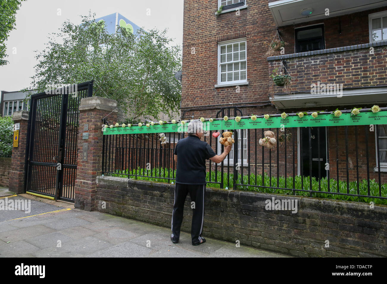 North Kensington, West London. UK 14 Jun 2019 - A man puts a white rose with the names of people who lost their lives, hung from railings on a block of flats to commemorate the second anniversary of the Grenfell Tower fire. On 14 June 2017, just before 1:00Êam a fire broke out in the kitchen of the fourth floor flat at the 24-storey residential tower block in North Kensington, West London, which took the lives of 72 people. More than 70 others were injured and 223 people escaped.  Credit: Dinendra Haria/Alamy Live News - Stock Image