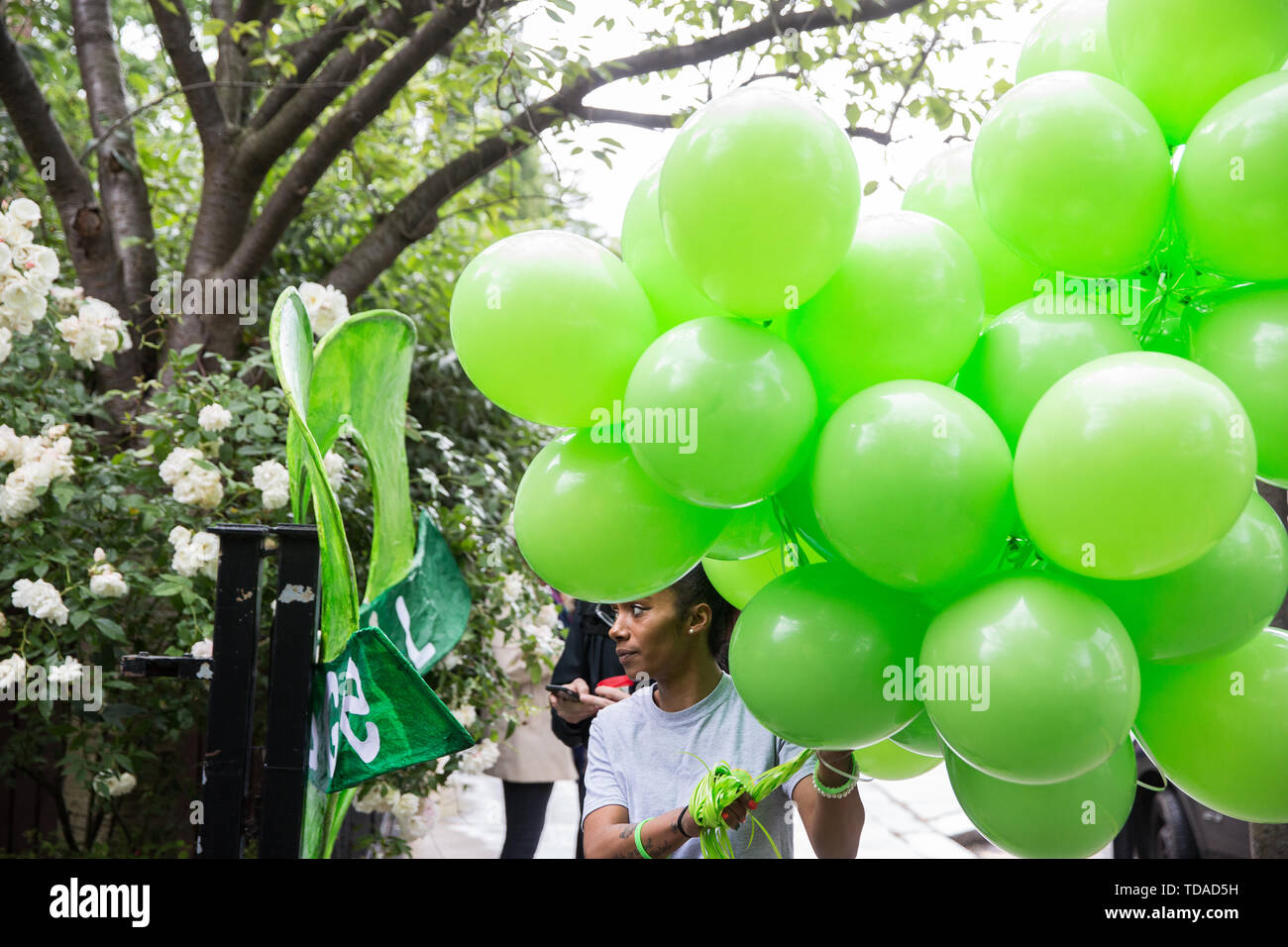 London, UK. 14 June, 2019. Green balloons are carried into a memorial service at St Helen's Church to mark the second anniversary of the Grenfell Tower fire on 14th June 2017 in which at least 72 people died and over 70 were injured. Credit: Mark Kerrison/Alamy Live News - Stock Image