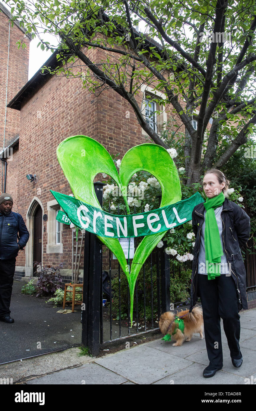 London, UK. 14 June, 2019. A dog and its owner, both wearing Green for Grenfell scarves, arrive to attend a memorial service at St Helen's Church to mark the second anniversary of the Grenfell Tower fire on 14th June 2017 in which at least 72 people died and over 70 were injured. Credit: Mark Kerrison/Alamy Live News - Stock Image