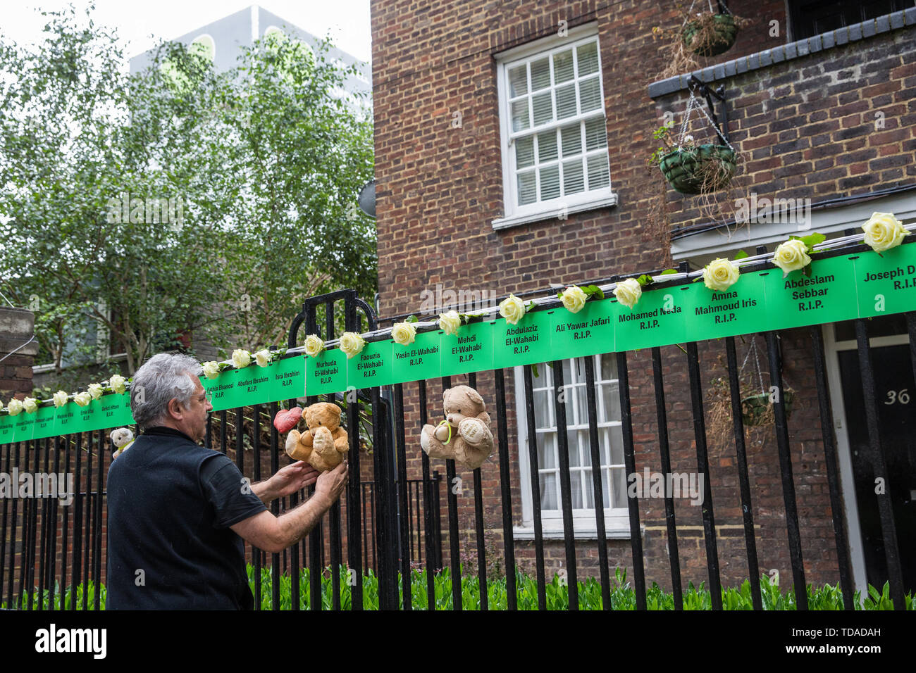 London, UK. 14 June, 2019. A man adjusts tributes to those who lost their lives in the Grenfell Tower fire beneath the tower on the second anniversary of the tragedy on 14th June 2017 which claimed the lives of 72 people and injured over 70 more. Credit: Mark Kerrison/Alamy Live News - Stock Image