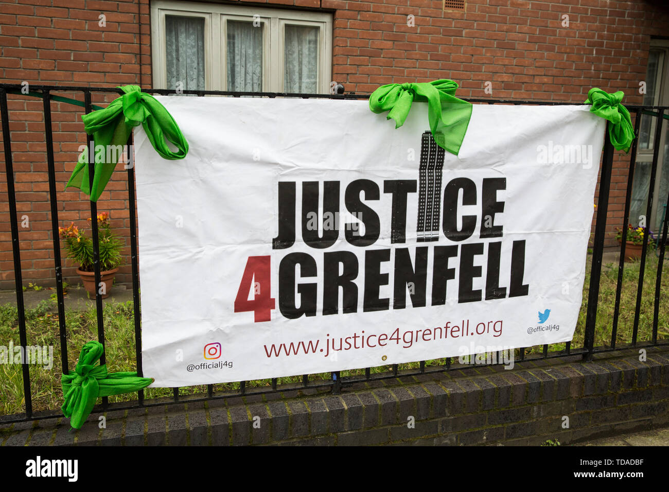 London, UK. 14 June, 2019. A Justice4Grenfell banner and Green for Grenfell scarves close to Grenfell Tower on the second anniversary of the Grenfell Tower fire on 14th June 2017 which claimed the lives of 72 people and injured over 70 more. Credit: Mark Kerrison/Alamy Live News - Stock Image