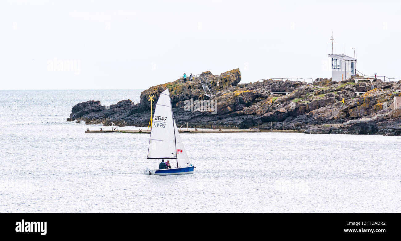 North Berwick, East Lothian, Scotland, United Kingdom. 14th June, 2019. UK Weather: After East Lothian suffered heavy rain the last few days, the weather has brightened, and people enjoy the outdoor pursuits in the seaside town. People sailing a dinghy in West Bay. Credit: Sally Anderson/Alamy Live News - Stock Image