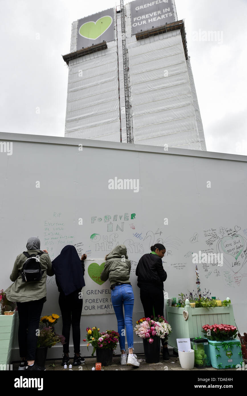Grenfell Tower, London, UK. 14th June, 2019. Writing commemorations on the wall next to the tower. The Grenfell Tower fire anniversary commemorations. Credit: Matthew Chattle/Alamy Live News - Stock Image