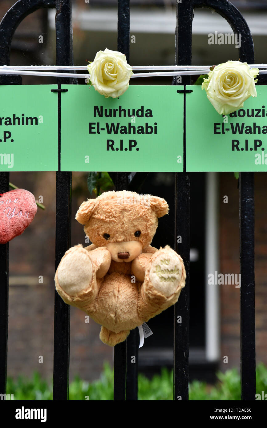 Grenfell Tower, London, UK. 14th June, 2019. The names of those who were lost in the fire on railings near the tower. The Grenfell Tower fire anniversary commemorations. Credit: Matthew Chattle/Alamy Live News - Stock Image
