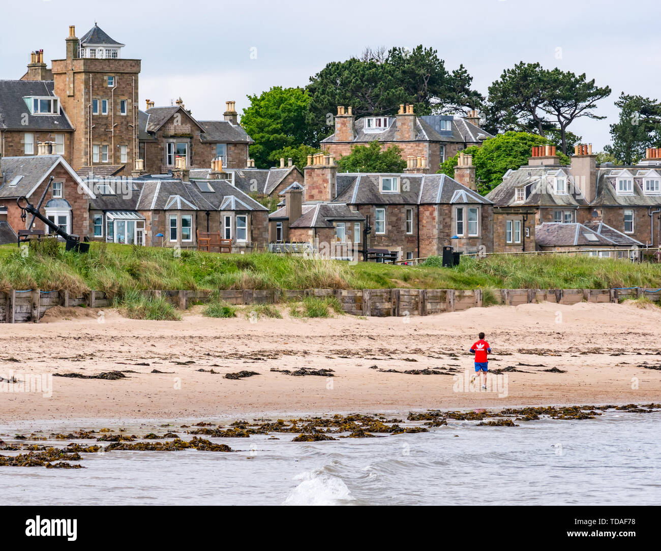 North Berwick, East Lothian, Scotland, United Kingdom, 14th June 2019. UK Weather: After East Lothian suffered heavy rain the last few days, the weather has brightened, and people enjoy the outdoor pursuits in the seaside town. A man jogging on West Bay beach. Credit: Sally Anderson/Alamy Live News - Stock Image