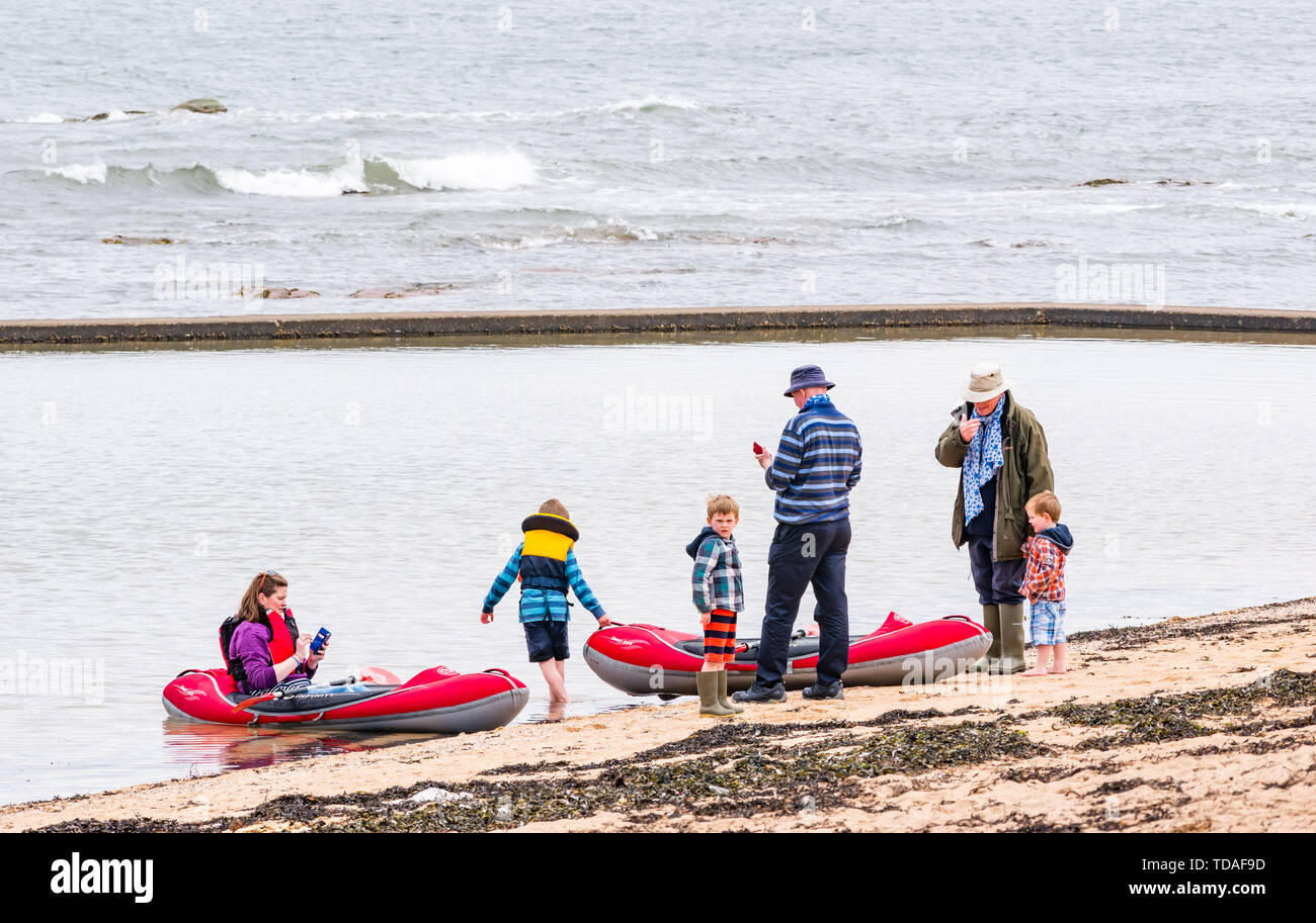 North Berwick, East Lothian, Scotland, United Kingdom, 14th June 2019. UK Weather: After East Lothian suffered heavy rain the last few days, the weather has brightened, and people enjoy the outdoor pursuits in the seaside town. A family with rubber dinghies in the tidal bathing pool at Milsey Bay.. Credit: Sally Anderson/Alamy Live News - Stock Image