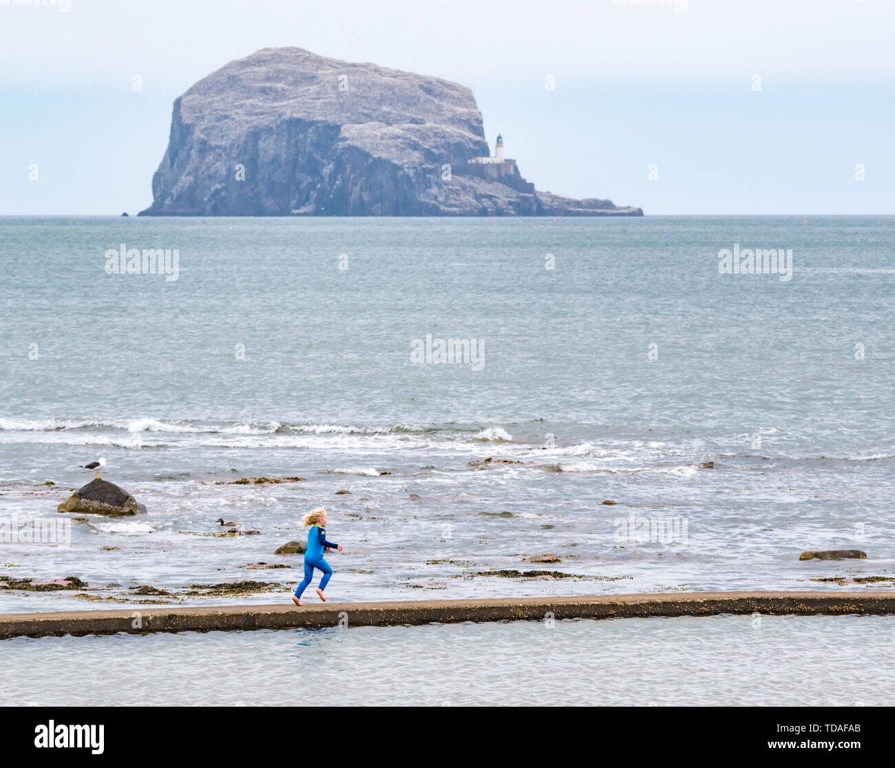 North Berwick, East Lothian, Scotland, United Kingdom, 14th June 2019. UK Westher: After East Lothian suffered heavy rain the last few days, the weather has brightened, and people enjoy the outdoor pursuits in the seaside town. A young girl enjoys running on rim of  the tidal bathing pool at Milsey Bay. Credit: Sally Anderson/Alamy Live News - Stock Image