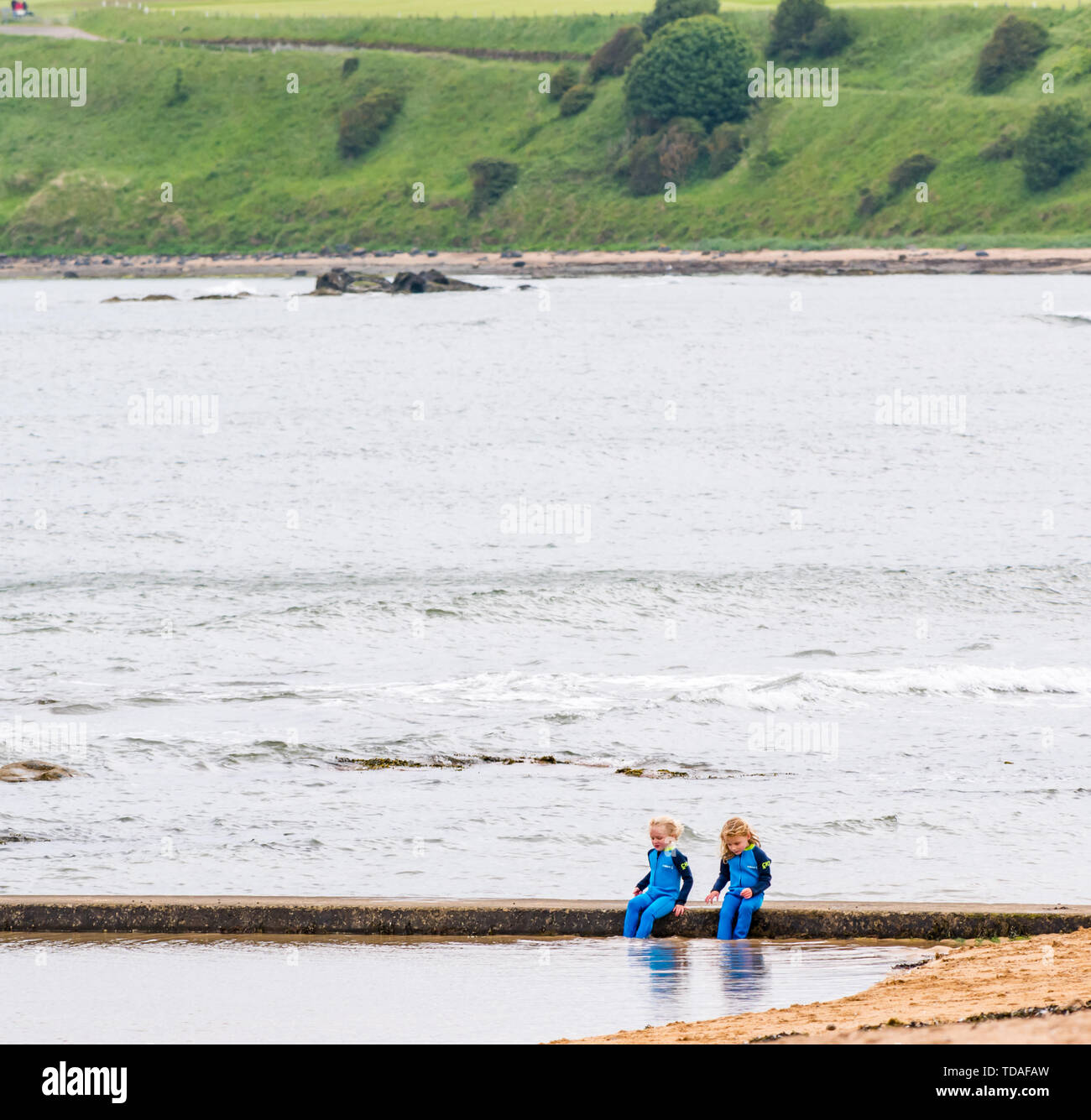 North Berwick, East Lothian, Scotland, United Kingdom, 14th June 2019. UK Weather: After East Lothian suffered heavy rain the last few days, the weather has brightened, and people enjoy the outdoor pursuits in the seaside town. Two young girls enjoy the tidal bathing pool at Milsey Bay. Credit: Sally Anderson/Alamy Live News - Stock Image